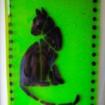 Black cat on green transparent glass