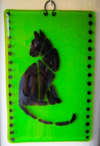 Black cat on green transparent glass