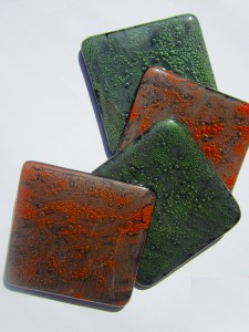 Set of four coasters with green and orange bubble effect on black glass.
